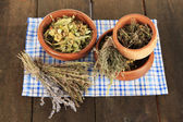 Medicinal Herbs in wooden bowls on napkin on wooden table — Stock Photo