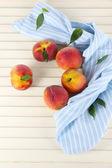 在木桌子上的餐巾纸上的桃子 — 图库照片