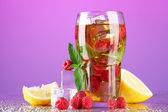 Iced tea with raspberries and mint on purple background — Stock Photo