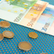 Euro banknotes and euro cents on blue background — Stock Photo