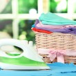 Steam iron and wicker basket with clothes, on bright background — Photo