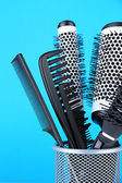 Iron basket with combs and round hair brushes, on color background — Stock Photo