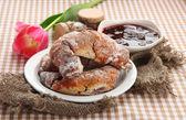 Taste croissants on plate and jam on tableclot — Stock Photo