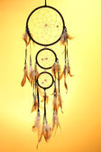 Beautiful dream catcher on yellow background — Stock Photo