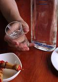 Berusad man dricker vodka på tabell närbild — Stockfoto