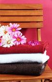 Handtücher und blumen auf holzstuhl auf braunen hintergrund — Stockfoto