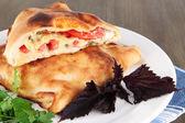 Pizza calzone en placa de servilleta de mesa de madera — Foto de Stock