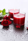 Beautiful romantic red candles with flowers, close up — Stock Photo