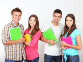 Group of happy beautiful young students at room — Stockfoto
