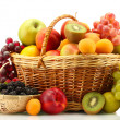 Assortment of exotic fruits and berries in baskets isolated on white — Stock Photo #28290365