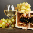 Stock Photo: Wooden case with wine bottle, wineglass and grape on wooden table on grey background