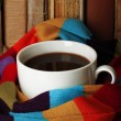 Cup of coffee wrapped in scarf on books background — Stock Photo #28291755