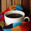 Cup of coffee wrapped in scarf on books background — Stok fotoğraf #28291755