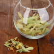 Dried herb in glass container on wooden table close-up — Stock Photo #28293135