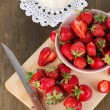 Strawberries in bowl on board cutting on wooden table — Stock Photo