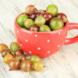 Stock Photo: Fresh gooseberries in cup on table close-up