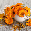Medicine bottles and calendula flowers on wooden background — Stock Photo