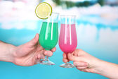 Cocktails in men's and women's hands on pool background — Stockfoto