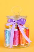 Glass jar containing various colored thread on yellow background — Stock Photo