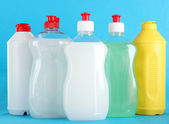 Bottles of dishwashing liquid on color background — Stock Photo