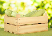Fresh marrows in wooden box, on bamboo mat, on bright background — Stock Photo