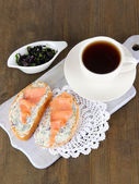 Fish sandwiches and cup of tea on cutting board on wooden table — Stock Photo