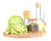 Green cabbage, oil, spices on cutting board, isolated on white — Stock Photo