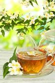 Kopp te med jasmine, på träbord, på ljus bakgrund — Stockfoto