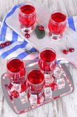 Glasses compote on board and metal tray on napkin on wooden table — Stock Photo