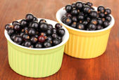 Fresh black currant in bowls on wooden background — Stock Photo