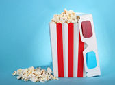 Popcorn and 3D glasses on blue background — Stock Photo