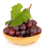 Ripe delicious grapes in wicker basket isolated on white — Stock Photo
