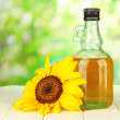 Stock Photo: Oil in jar and sunflower on wooden table close-up