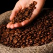 Coffee beans in hand on dark background — Stock Photo #28301791