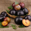 Rip plums on basket on sacking — Stock Photo #28302157