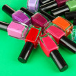 Group of bright nail polishes, on green background — Stock Photo #28302263