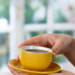 Cup in hands against window — Stock Photo