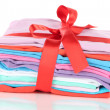 Pile of clothing with red ribbon and bow isolated on white — Stok fotoğraf