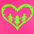 Green cut out paper heart with people inside, on color background — Stock Photo