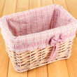 Wicket basket with pink fabric and bow, on wooden background — Stok Fotoğraf #28303711