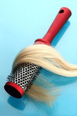 Comb brush with hair, on blue background — Stock Photo