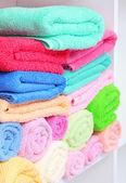 Serviettes colorées sur des étagères dans la salle de bain — Photo
