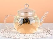Exotic green tea with flowers in glass teapot on table on color background.Process of making tea — Stock Photo