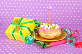 Colorful birthday cake with candle and gifts on pink background — Zdjęcie stockowe