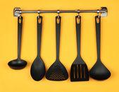 Black kitchen utensils on silver hooks, on yellow background — Stock Photo