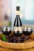 Composition of wine bottle, glasses and grape, on wooden tray, on bright background — Stock Photo