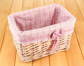 Wicket basket with pink fabric and bow, on wooden background — Stock Photo