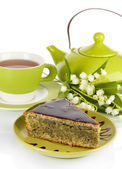 Delicious poppy seed cake with cup of tea isolated on white — Stock Photo