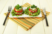 Tasty roasted marrow and tomato slices with salad leaves, on wooden background — Stock Photo