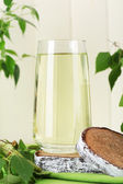 Glass of birch sap on green wooden table — Stock Photo